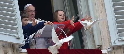 I bambini alla finestra con il papa lanciano le due colombe della pace su piazza San Pietro (Afp)